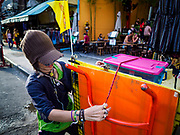 01 AUGUST 2018 - BANGKOK, THAILAND:     A vender shuts down their stand before being ticketed by Bangkok code enforcement officers on Khao San Road in Bangkok. Khao San Road is Bangkok's original backpacker district and is still a popular hub for travelers, with an active night market and many street food stalls. The Bangkok municipal government went through with it plans to reduce the impact of the street market on August 1 because city officials say the venders, who set up on sidewalks and public streets, pose a threat to public safety and could impede emergency vehicles. Venders are restricted to working from 6PM to midnight and fewer venders will be allowed to set up on the street. It's the latest in a series of night markets and street markets the city has closed.     PHOTO BY JACK KURTZ