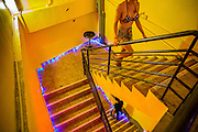 "19 JANUARY 2013 - BANGKOK, THAILAND:  A sex worker uses the stairs between the 2nd and 3rd levels of the Nana Entertainment Plaza in Bangkok. Prostitution in Thailand is technically illegal, although in practice it is tolerated and partly regulated. Prostitution is practiced openly throughout the country. The number of prostitutes is difficult to determine, estimates vary widely. Since the Vietnam War, Thailand has gained international notoriety among travelers from many countries as a sex tourism destination. One estimate published in 2003 placed the trade at US$ 4.3 billion per year or about three percent of the Thai economy. It has been suggested that at least 10% of tourist dollars may be spent on the sex trade. According to a 2001 report by the World Health Organisation: ""There are between 150,000 and 200,000 sex workers (in Thailand).""       PHOTO BY JACK KURTZ"
