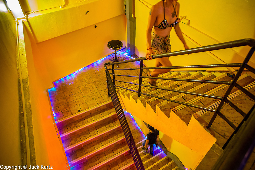 """19 JANUARY 2013 - BANGKOK, THAILAND:  A sex worker uses the stairs between the 2nd and 3rd levels of the Nana Entertainment Plaza in Bangkok. Prostitution in Thailand is technically illegal, although in practice it is tolerated and partly regulated. Prostitution is practiced openly throughout the country. The number of prostitutes is difficult to determine, estimates vary widely. Since the Vietnam War, Thailand has gained international notoriety among travelers from many countries as a sex tourism destination. One estimate published in 2003 placed the trade at US$ 4.3 billion per year or about three percent of the Thai economy. It has been suggested that at least 10% of tourist dollars may be spent on the sex trade. According to a 2001 report by the World Health Organisation: """"There are between 150,000 and 200,000 sex workers (in Thailand).""""       PHOTO BY JACK KURTZ"""