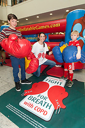"""Henry Wallis and Ben Mathison helped into thier boxing gloves by Jessica Law.at the launch of the """"Winning The Fight For Breath  with COPD Campaign"""" in Meadowhall Shopping Centre Sheffield on Saturday 18th February 2012..www.pauldaviddrabble.co.uk..18th February 2012 -  Image © Paul David Drabble"""