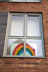 Rainbow painting in house window during Coronavirus lockdown, Norwich, UK April 2020