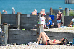 © Licensed to London News Pictures 22/07/2021. Whitstable, UK. A woman sunbathing on the beach. Another hot heatwave day as people enjoy a day out at Whitstable in Kent. Photo credit:Grant Falvey/LNP