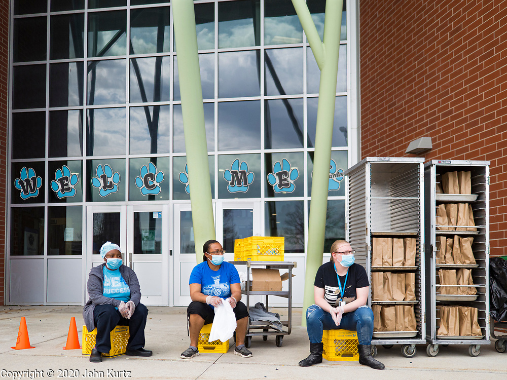 22 APRIL 2020 - DES MOINES, IOWA: FADYA HAROUN, left, SIMONA LEWIS, and KALY WOLFE wait for students during a grab and go lunch distribution at Edmunds Elementary School. Schools in Iowa are closed for the rest of the school year because of the COVID-19 (Coronavirus/SAR-CoV-2) pandemic. Des Moines Public Schools expanded their school lunch and distance learning efforts this week. Lunches are being distributed at all of the district's elementary and middle schools and officials have started distributing computers so students can participate in distance learning. The meal distribution was done according to social distancing guidelines.           PHOTO BY JACK KURTZ