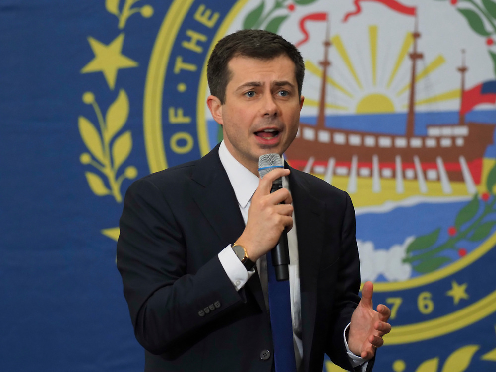 Democratic presidential candidate Pete Buttigieg addresses supporters at his Get Out the Vote rally in Milford, New Hampshire. Buttigieg is standing in front of an image of NH's state seal. This is his second to last campaign rally prior to the Tuesday, February 11 primary.