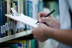 Young man writing on clipboard in library (Credit Image: © Image Source/Albert Van Rosendaa/Image Source/ZUMAPRESS.com)