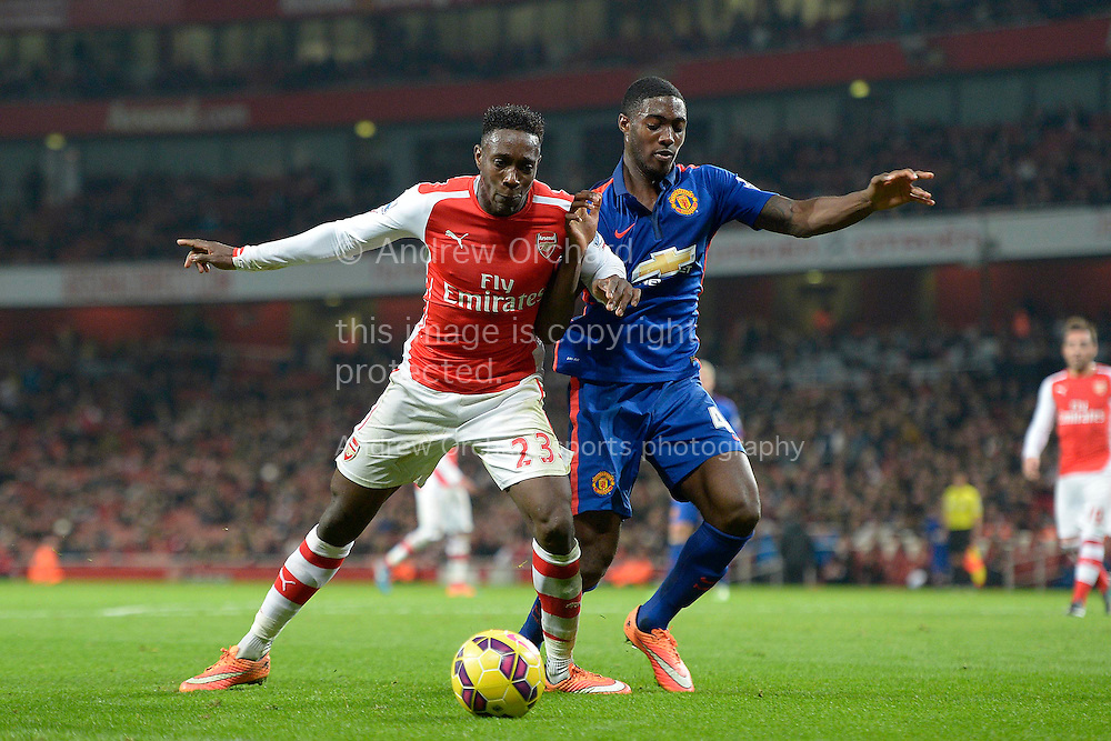 Danny Welbeck of Arsenal competing with Tyler Blackett of Manchester United. Barclays Premier league match, Arsenal v Manchester Utd at the Emirates Stadium in London on Saturday 22nd November 2014.<br /> pic by John Patrick Fletcher, Andrew Orchard sports photography.