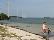 mother and child walking along the beach with in the background the 7 miles bridge Florida Keys
