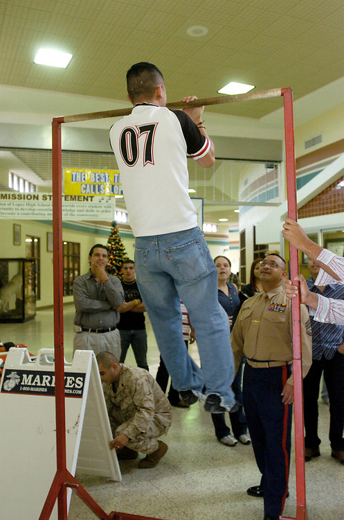 Brownsville, TX January, 2006:  Marine recruiter visits with a chin-up bar display at lunchtime  to help attract recruits. ©Bob Daemmrich/