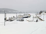 A woman walks past several boats which are stuck in the frozen lake of Jyvasjarvi during a blizzard Jyvaskyla, Central Finland