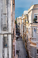 The view of the ancient narrow street of Calle San Jose in Cadiz looks from the third floor to the cobblestone street below.