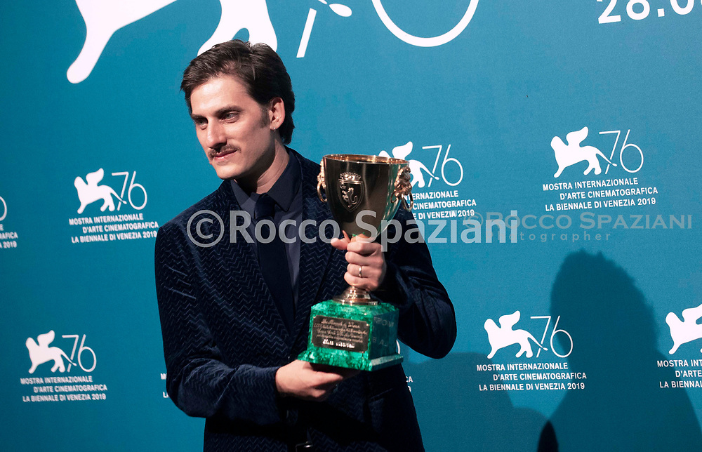 """Italian actor Luca Marinelli holds the Coppa Volpi for Best Actor he received for the movie """"Martin Eden"""" during the awards ceremony winners photocall of the 76th Venice Film Festival on September 7, 2019"""
