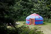 Blue and red yurt in a wooded area, Organic community farming project, Devon, UK