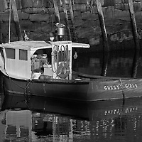 B&W Massachusetts photography of Rockport Harbor featuring the red fishing boat Gussy's Girls on a beautiful sunset night. This harbor is located on Cape Ann, north of Boston. <br />