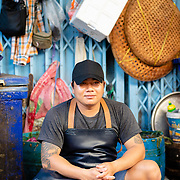 Portrait of young Thai fishmonger taking a rest at Khlong Toei market, Bangkok