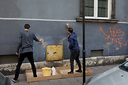 Two young Polish men paint a wall whose surface has been covered in graffiti in central Krakow, on 24th September 2019, in Krakow, Malopolska, Poland.