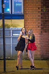 """© Licensed to London News Pictures . 16/12/2017. Manchester, UK. A woman leans on another women at Deansgate Locks . Revellers out in Manchester City Centre overnight during """" Mad Friday """" , named for historically being one of the busiest nights of the year for the emergency services in the UK . Photo credit: Joel Goodman/LNP"""