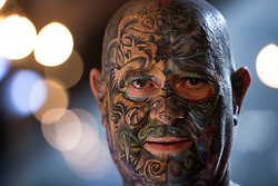 A man shows off his tattoos during the International tattoo convention at Tobacco Dock in east London.