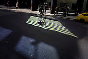 A cyclist pedals through green reflected light shining from a City of London office building.