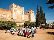 Children on a school trip sitting outside the fortified castle walls of the historic Alcazaba, of the Alhambra, Granada, Spain