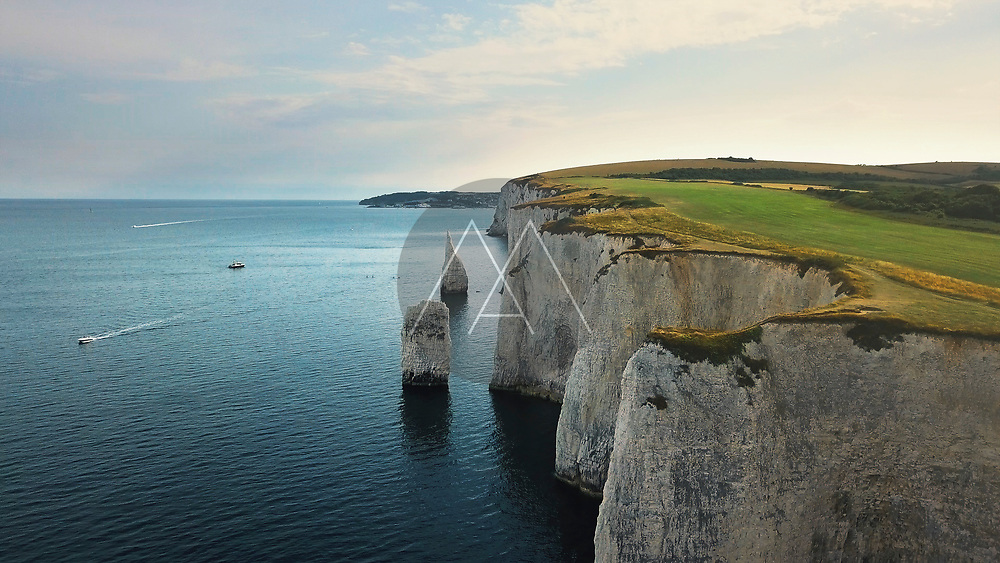 Aerial view of the Old Harry Rocks white cliffs and solitary pinnacles in the late afternoon in Studland, Dorset, United Kingdom.