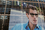 With corporate offices reflected in the window, an image of a male model looks out of the window of a menswear retailer near Liverpool Street Station in the City of London, the capitals financial district - aka the Square Mile, on 8th August, in London, England.