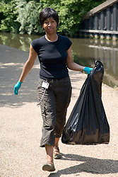 Woman carrying a refuse sack of rubbish,
