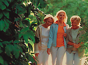 Three women walk together through a botanical garden
