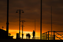 © Licensed to London News Pictures.<br /> Aberystwyth UK, 26/03/2019<br /> A beautiful sunset , at the end of another day of warm spring sunshine, silhouettes people walking along the promenade  in Aberystwyth, on the Cardigan Bay coast of west Wales. High pressure continues to dominate the weather for much of the UK, with settled conditions and clear blue skies<br /> photo Keith Morris/LNP