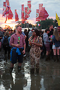 Party people stuck in mud chatting in the setting sun at Glastonbury Festival 25th July 2016, Somerset, United Kingdom.  The Glastonbury Festival runs over 3 days and has 3000 acts, including music, art and performance and approx. 150.000 attend the anual event.