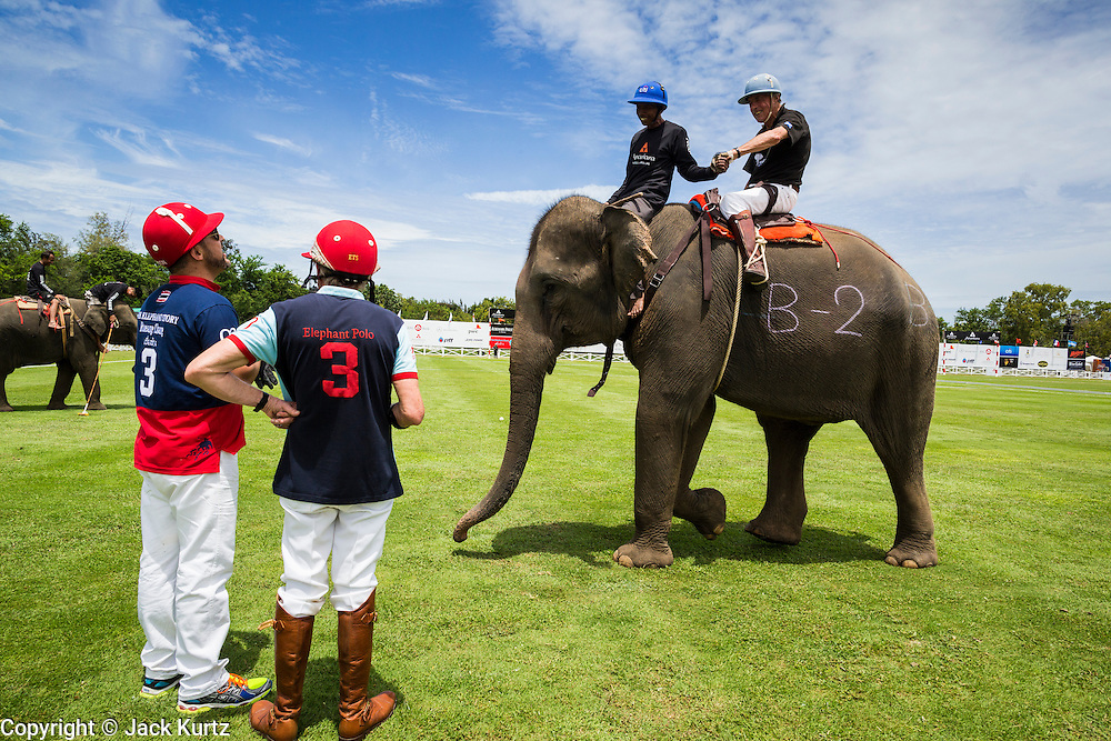 """28 AUGUST 2013 - HUA HIN, PRACHUAP KHIRI KHAN, THAILAND: JASON FRIEDMAN (left) and ED STORY talk to another polo player atop an elephant at the King's Cup Elephant Polo Tournament in Hua Hin, Thailand. The tournament's primary sponsor in Anantara Resorts and the tournament is hosted by Anantara Hua Hin. This is the 12th year for the King's Cup Elephant Polo Tournament. The sport of elephant polo started in Nepal in 1982. Proceeds from the King's Cup tournament goes to help rehabilitate elephants rescued from abuse. Each team has three players and three elephants. Matches take place on a pitch (field) 80 meters by 48 meters using standard polo balls. The game is divided into two 7 minute """"chukkas"""" or halves. There are 16 teams in this year's tournament, including one team of transgendered """"ladyboys.""""     PHOTO BY JACK KURTZ"""