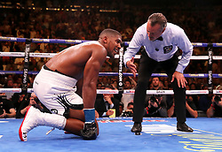 Anthony Joshua (left) spits his gum shield onto the floor as referee Mike Griffin starts a count during the match against Andy Ruiz Je at Madison Square Garden, New York.