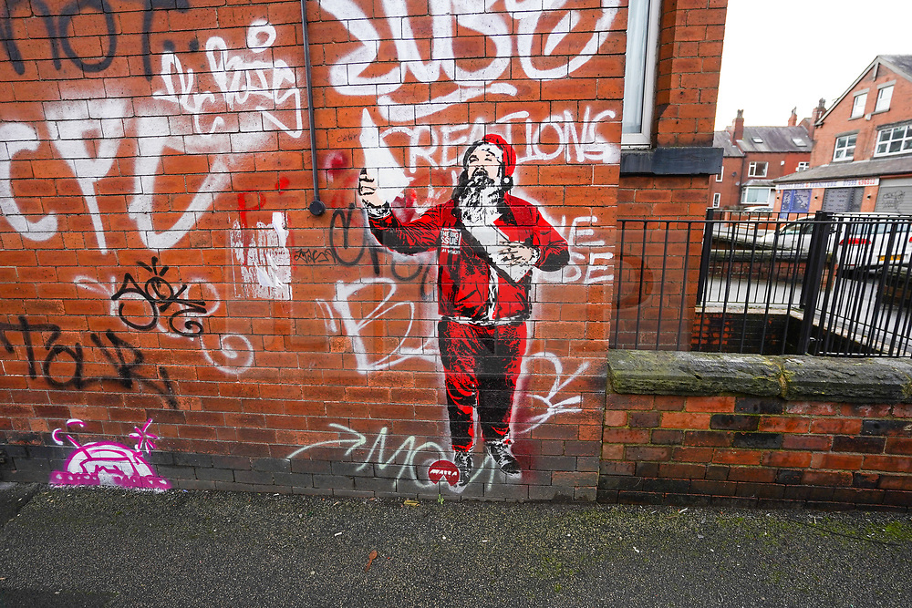 © Licensed to London News Pictures. 10/01/2021. Leeds, UK.  A new mural of a Big Issue seller dressed in a Santa outfit has appeared on a brick wall in Leeds. It is believed this new art work has been painted by Bansky. Photo credit: Ioannis Alexopoulos/LNP