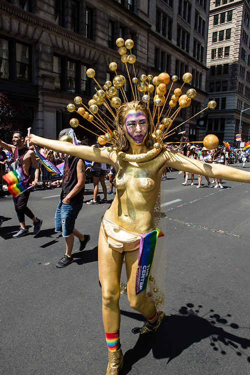 New York, NY - 30 June 2019. The New York City Heritage of Pride March filled Fifth Avenue for hours with participants from the LGBTQ community and it's supporters. A woman wears gold body paint and a sort of a headdress with many gilt balls.