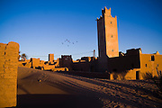 The setting sun illuminates the crumbling walls and mosque minaret of Ait Bounou, an ancient kasbah, or fortified village, in the Moroccan Sahara on November 8, 2007. The town is quickly falling into ruin as the inhabitants flee the drying well and the advancement of the dunes expedited by a 16-year drought and the damming of the Draa River.