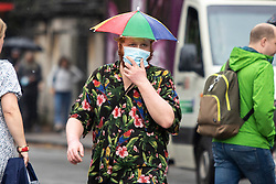 © Licensed to London News Pictures. 19/09/2021. London, UK. A man wears an umbrella hat during a rain shower in Greenwich, South East London. A yellow weather warning for rain is in place for parts of England.  Photo credit: George Cracknell Wright/LNP