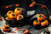 Persimmons styled with antique colander