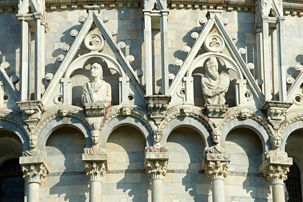 Medieval Sculptures of the  exterior of the Bapistry of Pisa, Italy . The Pisa Baptistery of St. John is a Roman Catholic ecclesiastical building in Pisa, Italy. Construction started in 1152 to replace an older baptistery, and when it was completed in 1363, it became the second building, in chronological order, in the Piazza dei Miracoli, near the Duomo di Pisa . The largest baptistery in Italy, it is 54.86 m high, with a diameter of 34.13 m. The Pisa Baptistery is an example of the transition from the Romanesque style to the Gothic style: the lower section is in the Romanesque style, with rounded arches, while the upper sections are in the Gothic style, with pointed arches. The Baptistery is constructed of marble, as is common in Italian architecture.