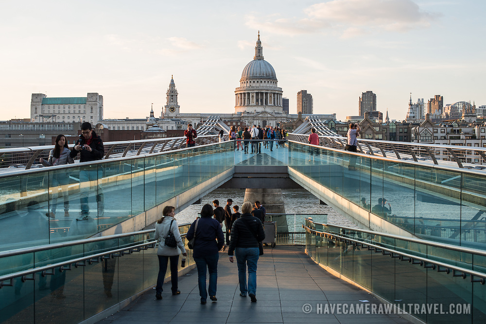 Pedestrians walking on Millenium Bridge across the River Thames. In the distance in center of frame is the dome of St Paul's Cathedral, one of the most distinctive of London's landmarks. There has been a church on this site since 604 AD. The current building, with it's massive dome, was designed by Christopher Wren and dates back to the late 17th century.