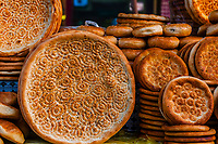 Nang (flatbread) at street market in Bazaar,  Kashgar, an oasis city in Xinjiang Province, China.  It is the westernmost city in China, located near the border with Afghanistan, Kyrgyzstan, Pakistan, and Tajikistan. It was a stop on the Silk Road. Uyghur people are a Central Asian people of Muslim Turkic origin. They are China's largest minority group.