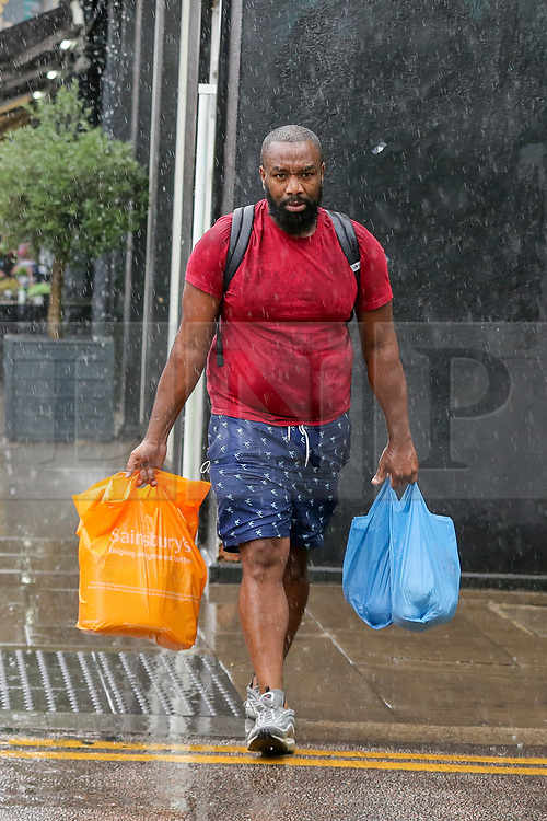 © Licensed to London News Pictures. 28/07/2021. London, UK. A shopper is caught during a torrential downpour in north London. According to The Met Office, wet weather is expected in the capital for this week. Photo credit: Dinendra Haria/LNP