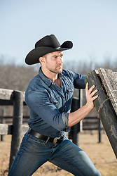 cowboy working fixing a fence on a ranch