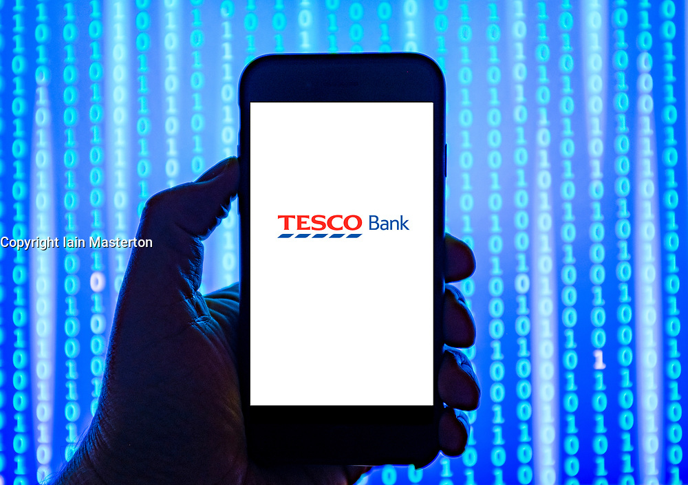 Person holding smart phone with Tesco Bank   logo displayed on the screen. EDITORIAL USE ONLY