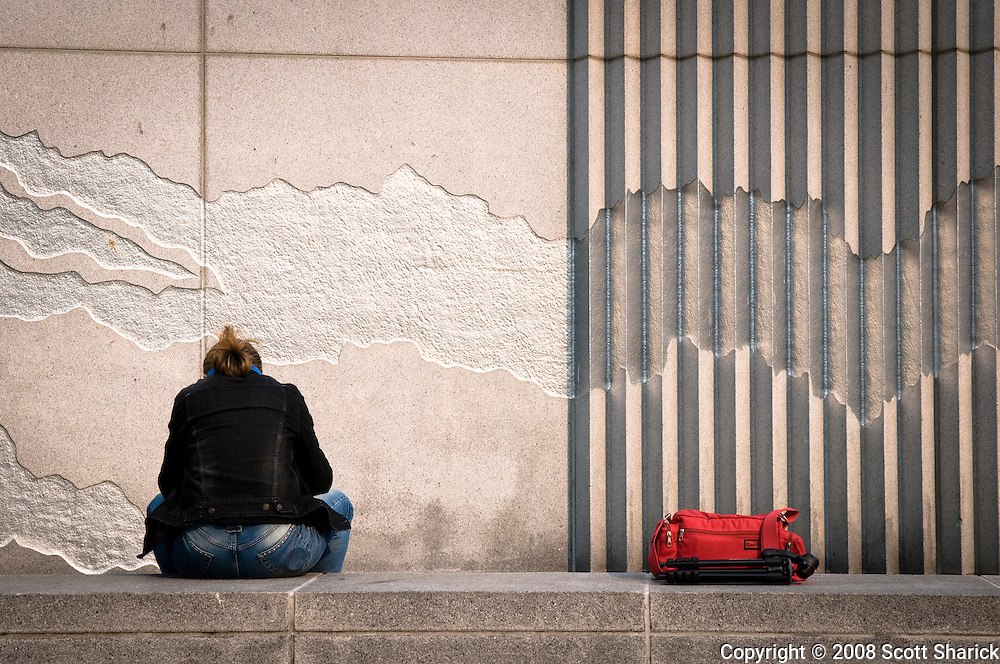 A woman sits on a stone ledge with her red backpack near her in this picture of California.