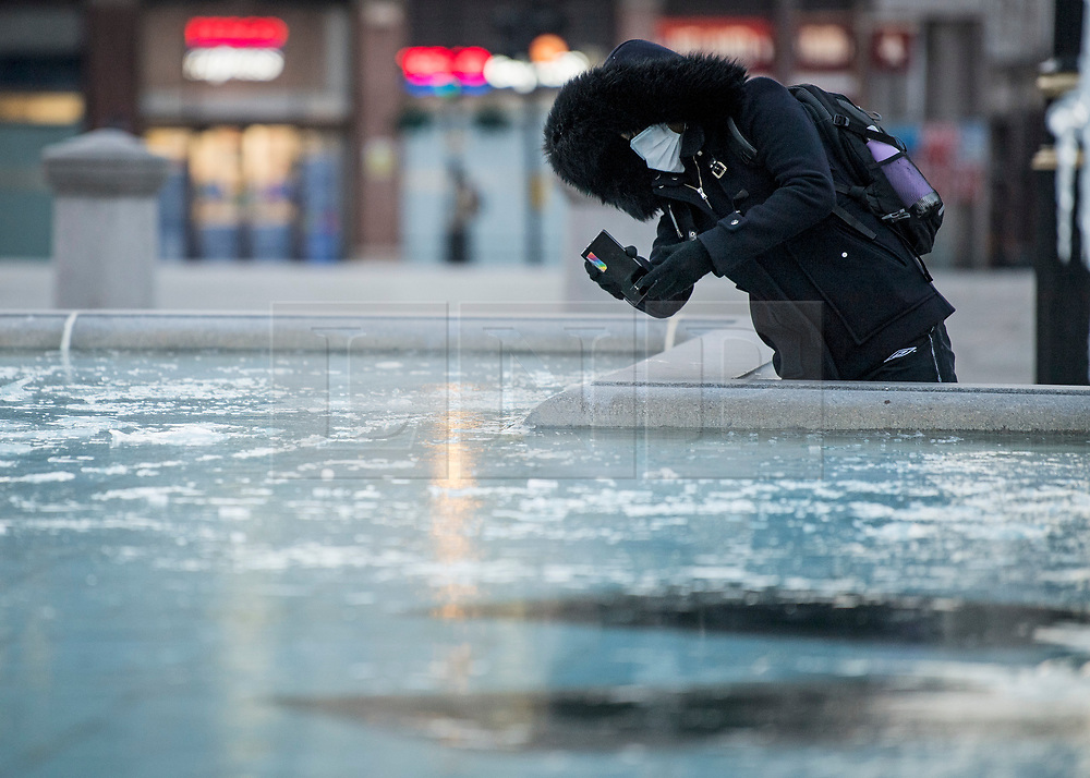 © Licensed to London News Pictures. 13/02/2021. London, UK. A member of the public takes a picture of The fountains at Trafalgar Square in central London, which remain frozen over following another night of sub zero temperatures in the capital. Photo credit: Ben Cawthra/LNP