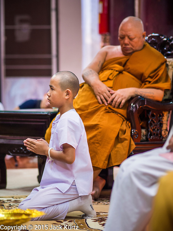 """06 APRIL 2015 - CHIANG MAI, CHIANG MAI, THAILAND:  A boy being ordained as a novice monk prays in front of a senior monk during the boy's ordination on the last day of the three day long Poi Song Long Festival in Chiang Mai. The Poi Sang Long Festival (also called Poy Sang Long) is an ordination ceremony for Tai (also and commonly called Shan, though they prefer Tai) boys in the Shan State of Myanmar (Burma) and in Shan communities in western Thailand. Most Tai boys go into the monastery as novice monks at some point between the ages of seven and fourteen. This year seven boys were ordained at the Poi Sang Long ceremony at Wat Pa Pao in Chiang Mai. Poy Song Long is Tai (Shan) for """"Festival of the Jewel (or Crystal) Sons.  PHOTO BY JACK KURTZ"""