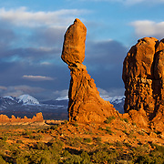Balanced Rock is a popular landmark at Arches National Park in Moab, UT. The large boulder perched atop a relatively slender pillar of rock is the size of three school buses. The boulder and pillar are made of two different types of stone, so they are wearing away at different rates. Balanced Rock is 128 feet (39 m) high and the boulder weighs approximately 3,577 tons.