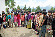 Children queueing up for lunch at a rural boarding school during the weekend in Radhi village, Bhutan. Most villages have a primary school although in very remote areas it is not uncommon for children to board even during the early years. Lunch usually consists of potato soup and rice.