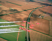 Banking slowly left over the agricultural Lincolnshire countryside are the elite 'Red Arrows', Britain's prestigious Royal Air Force aerobatic team, who have commenced an In-Season Practice (ISP) training flight near their base at RAF Scampton. They turn at a gentle angle trailing white organic smoke  before reforming in front of a local crowd at the airfield and working through a 25-minute series of display manoeuvres that are loved by thousands at summer air shows. Their objective is to appear perfectly spaced from a ground perspective. Freshly-ploughed English fields with properties, roads and hedgerows are seen below. After some time off, spare days like this are used to hone their manual aerobatic and piloting skills before re-joining the air show circuit. Since 1965 they've flown over 4,000 shows in 52 countries.