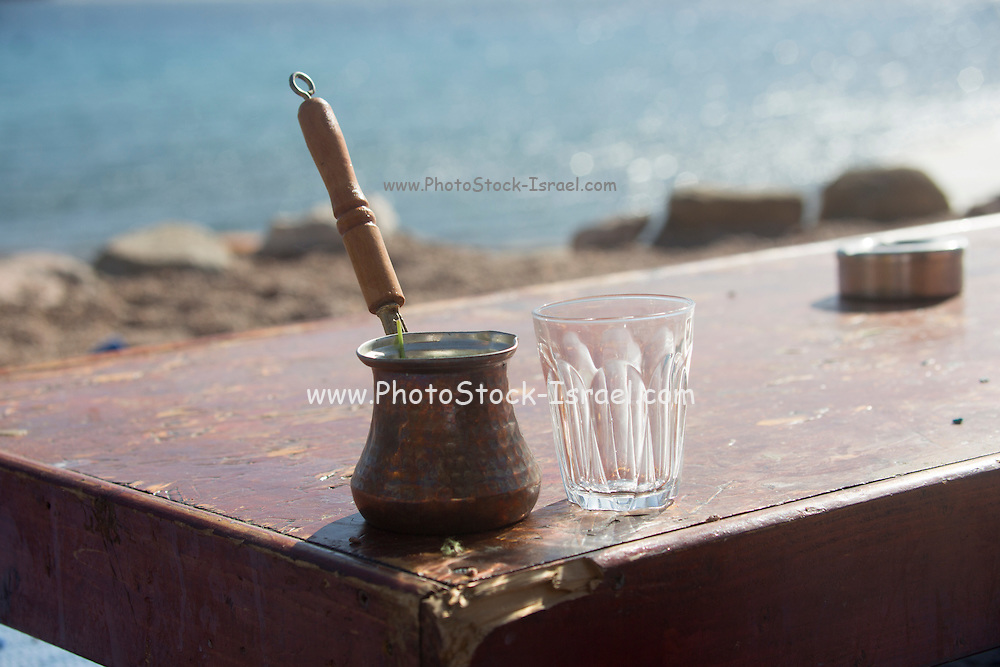 A pot of cooked (boiled or Turkish) coffee served outdoors with glass