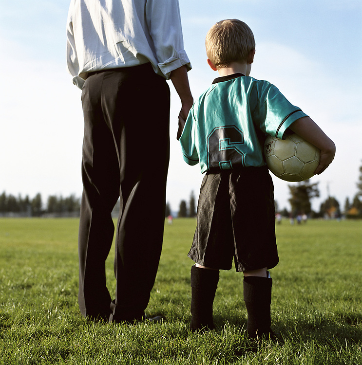 Man and boy together with soccer ball standing in a field together.